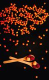 Orange sea-buckthorn background, isolated on a black background, falling down. Wooden spoons with raspberries and sea-buckthorn berries, close-up, natural Royalty Free Stock Image