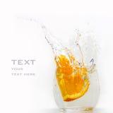 Orange segment falls in a glass. Water splashes royalty free stock photo