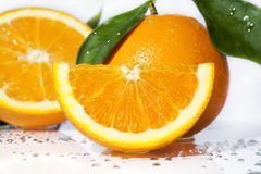 Orange Segment and Oranges. An orange segment on white surface with water droplets, whole orange with leaves and half orange in background Stock Photo