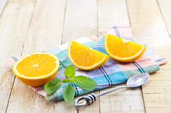 Orange segments slice with mint and stainless spoon on a pastel fabric and wooden background Stock Images