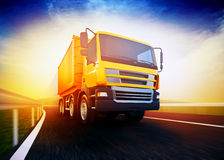 Orange semi-truck on blurry asphalt road under blue sky and suns. 3d rendered illustration of a orange semi-truck on blurry asphalt road under blue sky and Stock Image