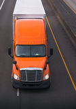 Orange semi truck with dry van trailer on the road top view. Orange semi truck with chrome grille and high roof move on the road with dry van trailer carry Royalty Free Stock Photo