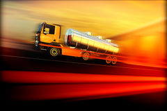 Orange semi truck with oil cistern on speed blured asphalt road. Highway at sunset - transportation background Royalty Free Stock Image