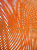 Orange sheet with open dots letting in bits lights Stock Images