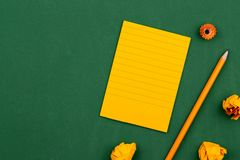 An orange sheet of paper lies on a green school board constituting a frame for text. near pencil and crumpled pages. Copy space. Flat lay Top view Concept royalty free stock images