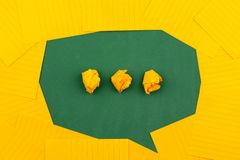Orange sheets of paper lie on a green school board and form a chat bubble with three crumpled papers.  stock images