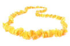 Orange, shiny amber necklace for the woman on white background Royalty Free Stock Photography