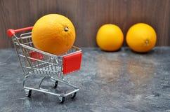 Orange in shopping cart royalty free stock photo