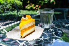 Orange shortcake in outdoor coffee shop. Orange shortcake and cool water in outdoor coffee shop Royalty Free Stock Photos