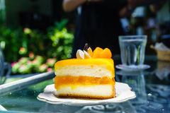 Orange shortcake in outdoor coffee shop. Orange shortcake and cool water in outdoor coffee shop royalty free stock images