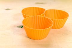 Orange silicone baking cups for muffins or cupcakes on solid wood background. Close up shot Royalty Free Stock Photography