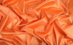 Orange silk. Background with some soft folds and highlights royalty free stock photography