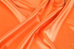 Orange silk. Background with some soft folds and highlights stock photos