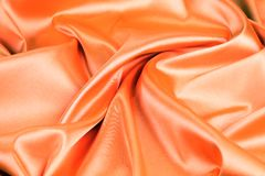 Orange silk background. With some soft folds and highlights Stock Images