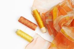 Orange silk and matching threads Stock Photo