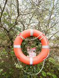 An orange and silver life buoy with rope with a safety sign behi Stock Photo