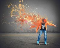 Orange skater. Boy with skate leaves a coloured trail Royalty Free Stock Image
