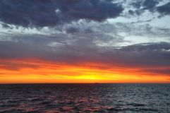 Orange Skies over the Indian Ocean, Western Australia. Bright orange skies just after sunset with the Indian Ocean water in Western Australia and clouds Stock Photo