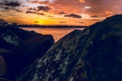 Orange Skies On The Rocks. Orange skies setting over rocks stock photography