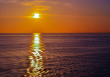 Orange Skies With Sun Setting Over the Ocean. Calm waters stock photo