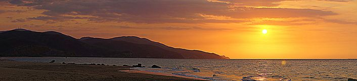 Sunset over beach, Playa San Luis, Venezuela. Orange skies at sunset over waves on sandy beach at Playa San Luis, Venezuela stock image