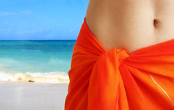 Orange skirt. Close-up of woman tummy in orange beach skirt on a sunny beach Stock Photos