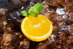 Orange skiva med mintkaramellbladet överst av iskuber Royaltyfria Foton
