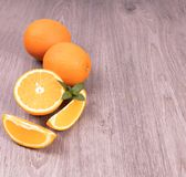 Orange skivor bredvid den hela citrusa garnerade mintkaramellen på en träyttersida fotografering för bildbyråer
