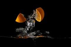 Orange skivor plaskar in i vätska på svart bakgrund Royaltyfria Bilder