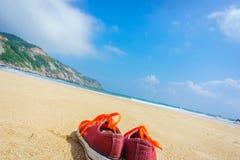 Orange skor sitter på en sandig strand Royaltyfria Bilder