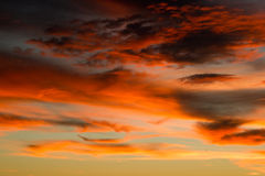 Orange sky filled with clouds during sunset. Sky filled with dark and light orange colored clouds during sunset Royalty Free Stock Photo