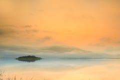 Orange sky and mist around mountain. Stock Photography