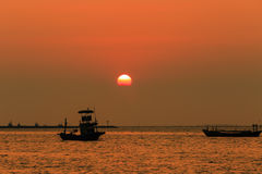 Orange sky with sunset over sea , shore and fishing boat Stock Image