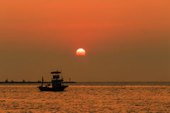 Orange sky with sunset over sea , shore and fishing boat Royalty Free Stock Image