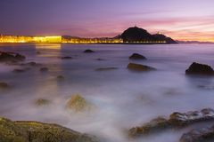 Orange sky at sunset, rocks and beach with the city of San Sebastian. In the background royalty free stock images