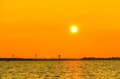 Orange skymning i New York med Verrazzano-trångt pass brosikt arkivfoto