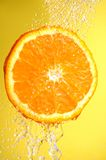 Orange slice. Under water on yellow background Stock Photo