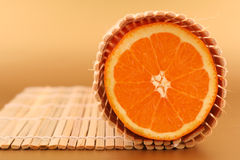 Orange slice. On bamboo matting royalty free stock photo