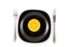 Orange slice on black plate Stock Photography