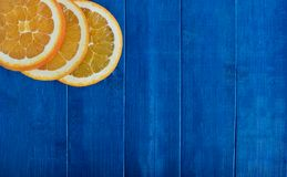Orange slice on blue background Royalty Free Stock Images