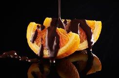 Orange slice in chocolate. On a black background Stock Photos