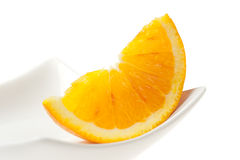 Orange Slice Closeup on White Plate Stock Photo
