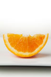 Orange Slice Closeup on White Plate Stock Images