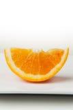 Orange Slice Closeup on White Plate Stock Images