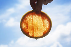 Orange slice dripping with juice in front of a bright sunwith blue sky background with white  clouds Stock Photo