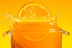 Orange slice falling into the liquid Stock Photography