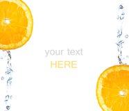 Orange slice falling and splashing Royalty Free Stock Images