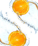 Orange slice falling and splashing Royalty Free Stock Image