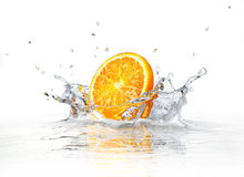 Orange slice falling and splashing into clear water. At white background royalty free stock images