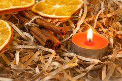 Orange slice and fragrant cinnamon sticks with a burning candle, close-up royalty free stock photos